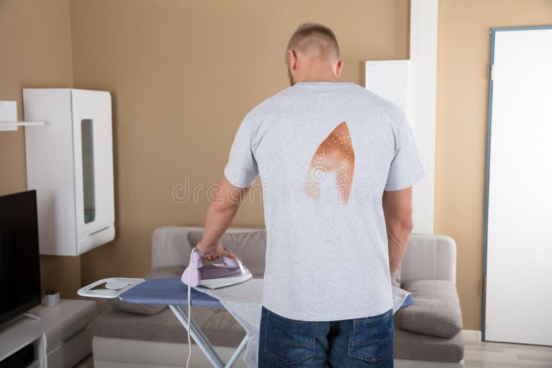 Vista posterior de un paño que plancha del hombre fotos de archivo libres de regalías
