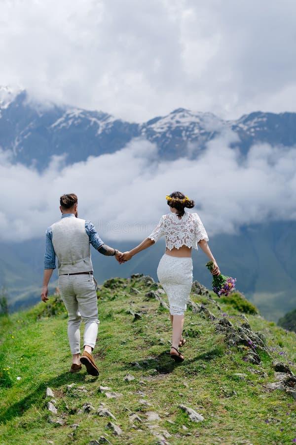 Vista posterior de un par joven en amor, llevando a cabo las manos y disfrutando de paisaje hermoso en las montañas imagenes de archivo