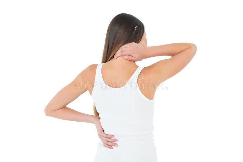 Vista posterior de una mujer casual que sufre del dolor del cuello imagenes de archivo