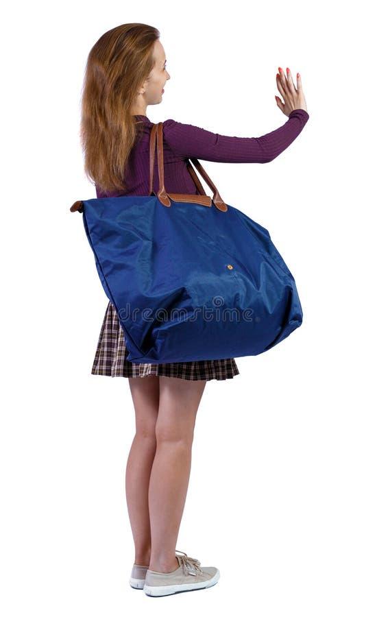 Vista posterior de una mujer con bolsa azul fotografía de archivo