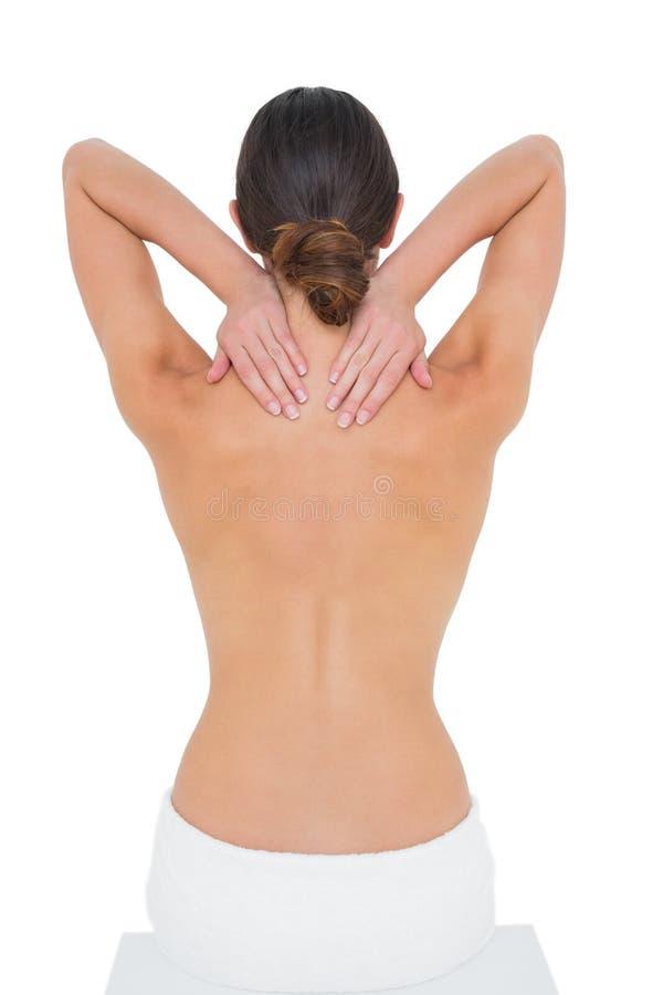 Vista posterior de una mujer con las tetas al aire que sufre del dolor del cuello imagen de archivo libre de regalías