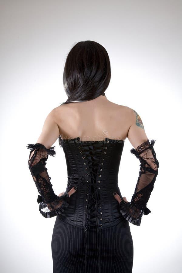 Vista posterior de una mujer en corsé negro fotografía de archivo