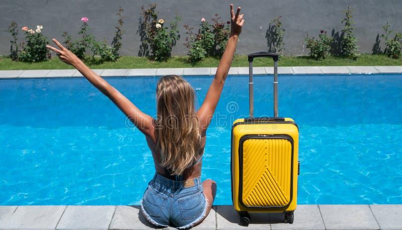 Vista posterior de una mujer feliz con maletas amarillas sentada al lado de la piscina imagen de archivo