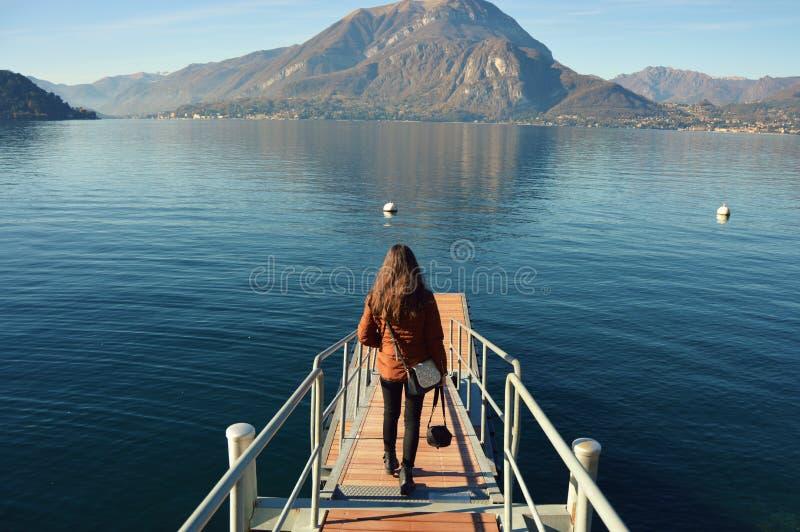 Vista posterior de una mujer illuminada en el embarcadero de Como del lago en Italia imagen de archivo