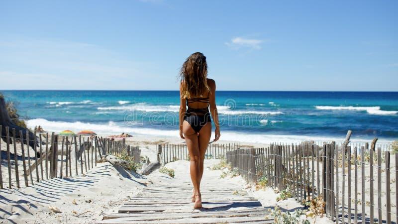 Vista posterior de una mujer joven hermosa que presenta en la playa Océano, playa, arena, fondo del cielo imagen de archivo