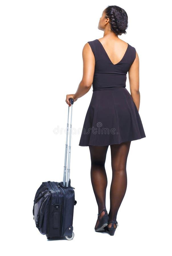 Vista posterior de una mujer negra elegante con una maleta mirando hacia arriba imagenes de archivo