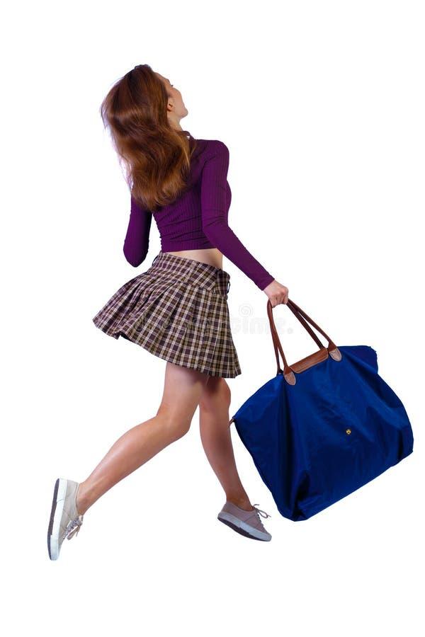 Vista posterior de una mujer que salta con bolsa azul foto de archivo libre de regalías