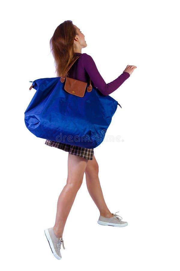 Vista posterior de una mujer que salta con bolsa azul foto de archivo