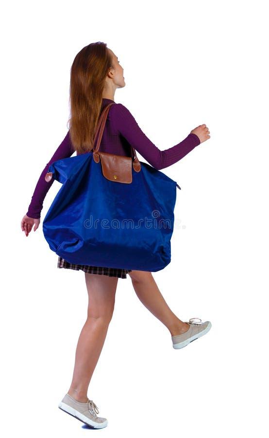 Vista posterior de una mujer que salta con bolsa azul imagen de archivo libre de regalías