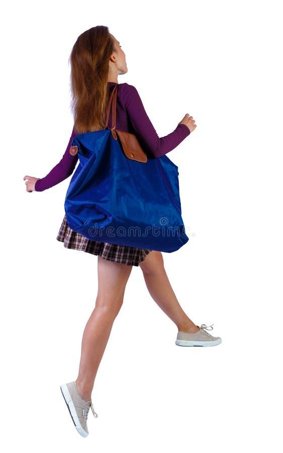 Vista posterior de una mujer que salta con bolsa azul imagen de archivo