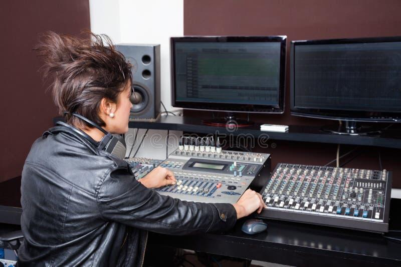 Vista posterior del audio de mezcla de la mujer joven fotografía de archivo libre de regalías