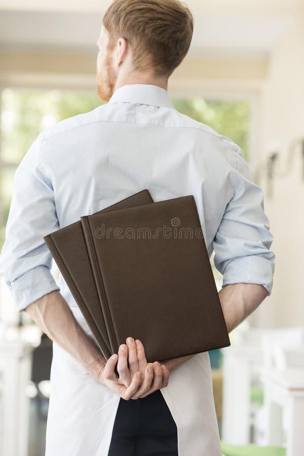 Vista posterior del camarero joven que lleva a cabo menús mientras que se coloca en el restaurante foto de archivo libre de regalías