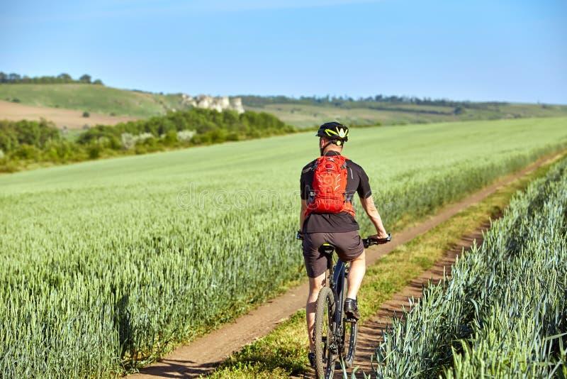 Vista posterior del ciclista joven con la mochila que completa un ciclo en la pista del campo fotografía de archivo libre de regalías