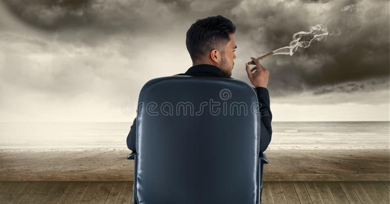 Vista posterior del cigarro que fuma del hombre de negocios mientras que se sienta en silla fotografía de archivo
