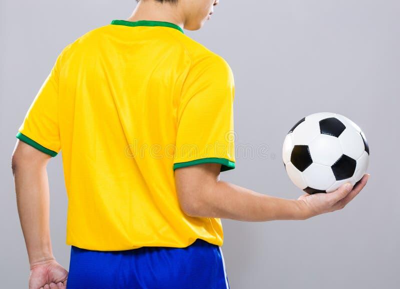 Vista posterior del control del futbolista con el balón de fútbol foto de archivo