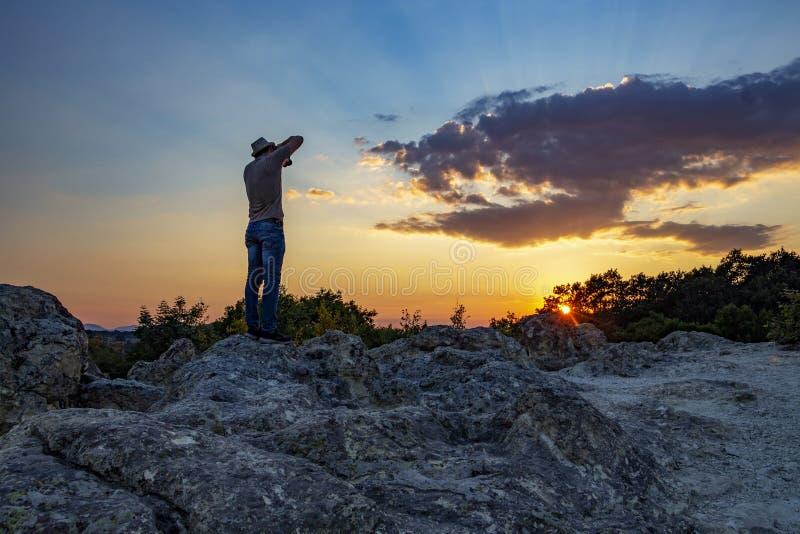 Vista posterior del fotógrafo de sexo masculino irreconocible que toma las imágenes de la puesta del sol sobre las setas de piedr imagenes de archivo