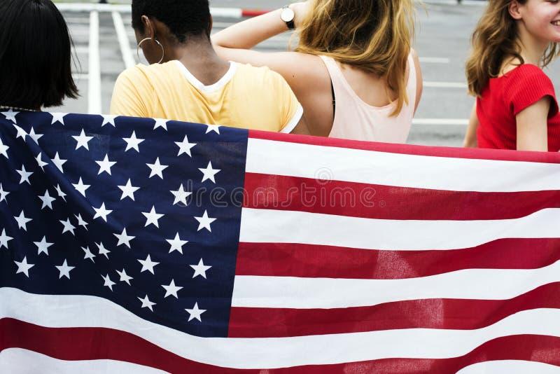 Vista posterior del grupo diverso de las mujeres con la bandera americana de la nación foto de archivo libre de regalías