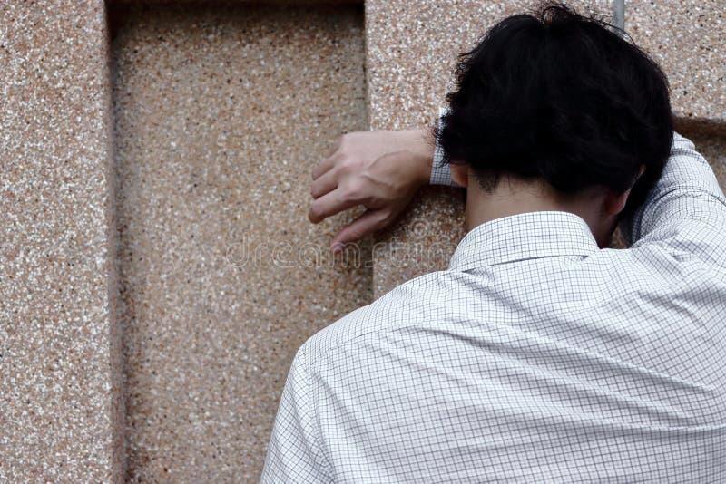 Vista posterior del hombre asiático joven cansado y preocupante en el griterío de la depresión foto de archivo
