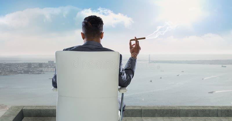 Vista posterior del hombre de negocios que se sienta en silla y el cigarro que fuma mientras que mira el mar contra el cielo fotografía de archivo