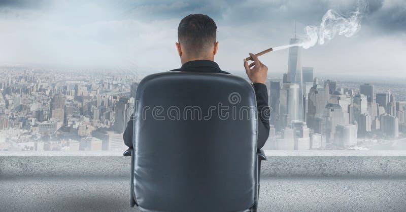 Vista posterior del hombre de negocios que se sienta en silla y que mira la ciudad mientras que fuma el cigarro fotografía de archivo