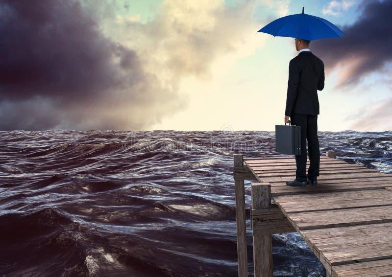 Vista posterior del hombre de negocios que sostiene el paraguas azul con la cartera y que mira el mar del st mientras que se colo stock de ilustración