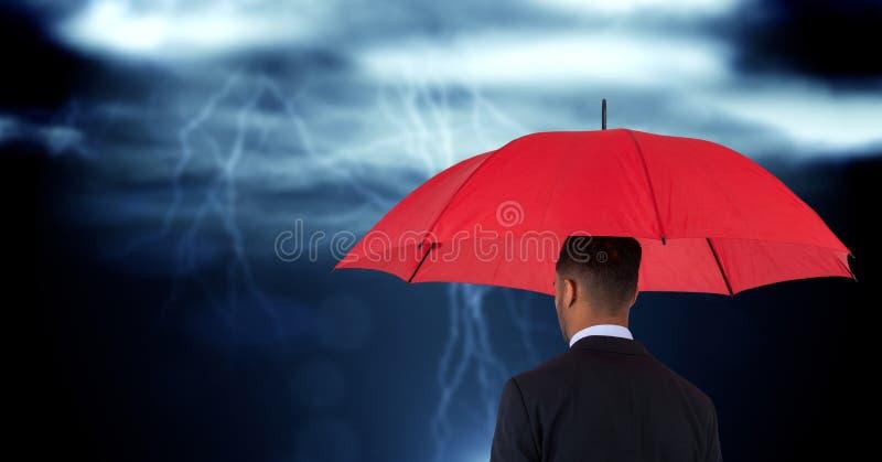 Vista posterior del hombre de negocios que sostiene el paraguas rojo contra la imagen compuesta digital de nubes fotografía de archivo