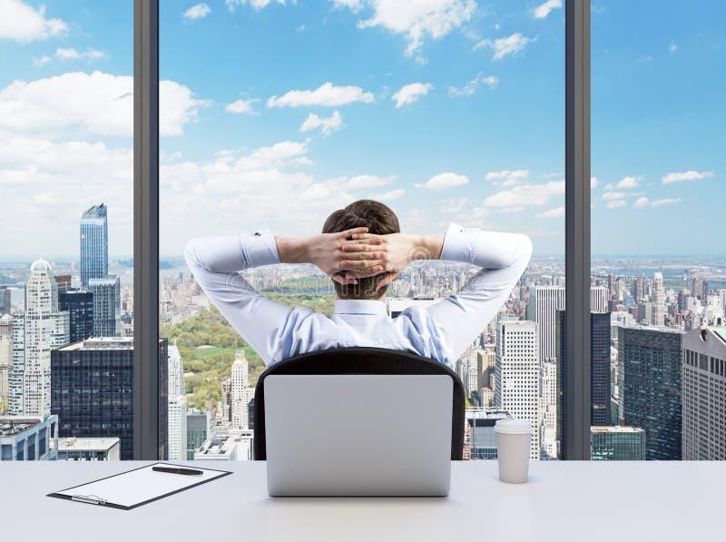 Vista posterior del hombre de negocios relajante con las manos cruzadas detrás de su cabeza, que está mirando el parque de Cntral foto de archivo libre de regalías