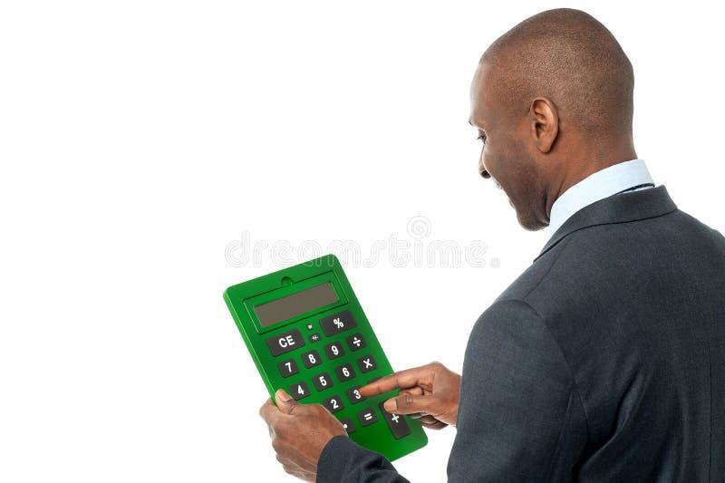 Vista posterior del hombre de negocios usando la calculadora fotografía de archivo libre de regalías