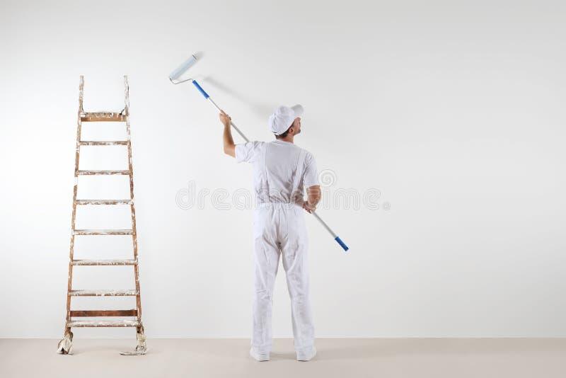 Vista posterior del hombre del pintor que mira la pared en blanco, con el palillo de la pintura fotografía de archivo libre de regalías