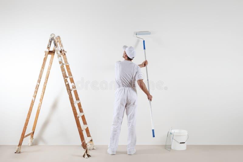 Vista posterior del hombre del pintor que mira la pared en blanco, con el palillo de la pintura fotografía de archivo