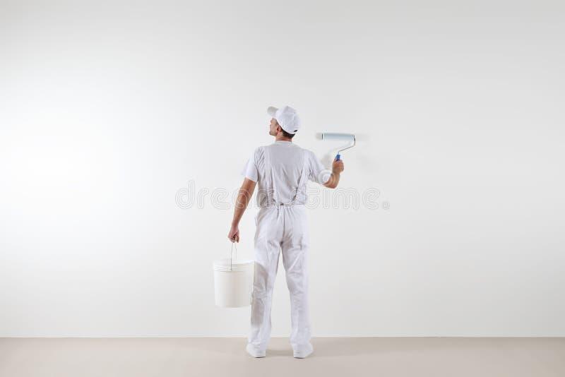Vista posterior del hombre del pintor que mira la pared en blanco, con el rolle de la pintura foto de archivo libre de regalías