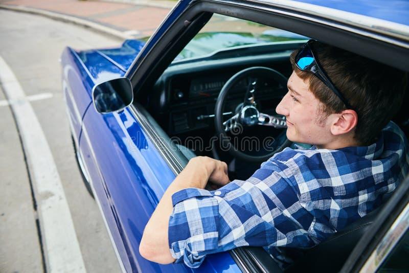 Vista posterior del hombre joven sonriente que se sienta en coche imagen de archivo libre de regalías