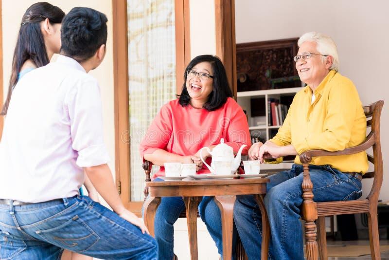 Vista posterior del hombre joven y de los padres que visitan de la mujer en casa fotografía de archivo