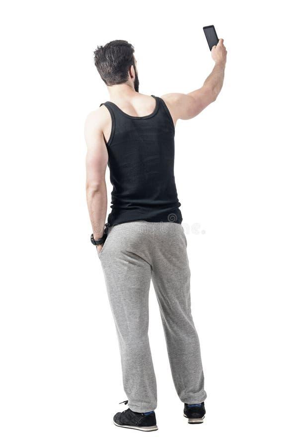Vista posterior del hombre muscular del gimnasio que toma la foto del selfie con el teléfono móvil foto de archivo libre de regalías