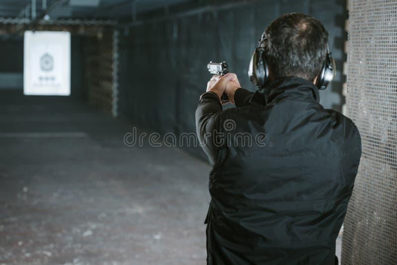 vista posterior del hombre que apunta el arma a la blanco foto de archivo libre de regalías