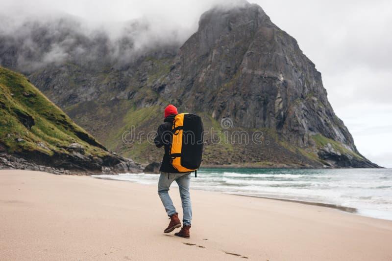Vista posterior del hombre turista con mochila caminando frente al macizo de la montaña mientras viaja por la playa del océano foto de archivo libre de regalías