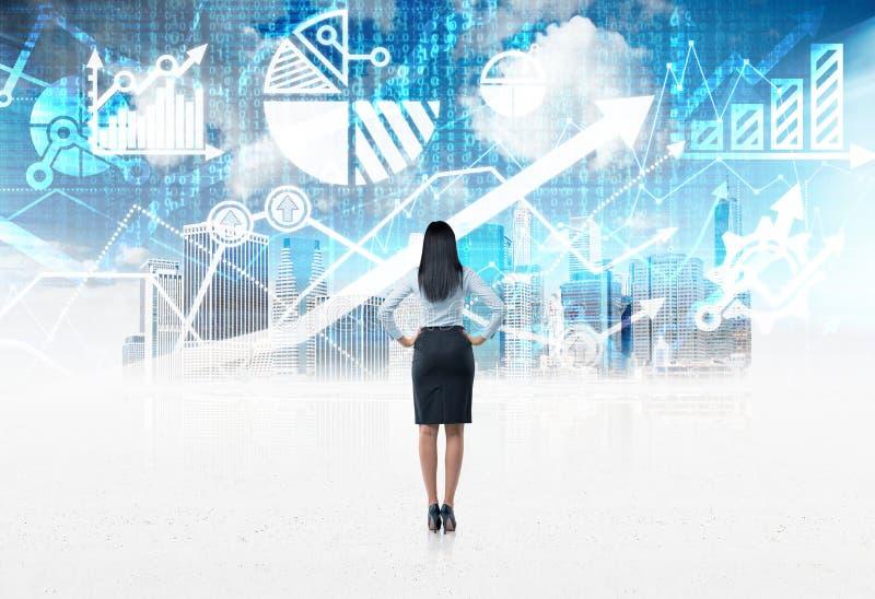 Vista posterior del integral de una señora del negocio que se coloca delante del fondo financiero digital azul de las cartas imagen de archivo