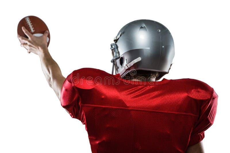 Vista posterior del jugador de fútbol americano en el jersey rojo que sostiene la bola imágenes de archivo libres de regalías