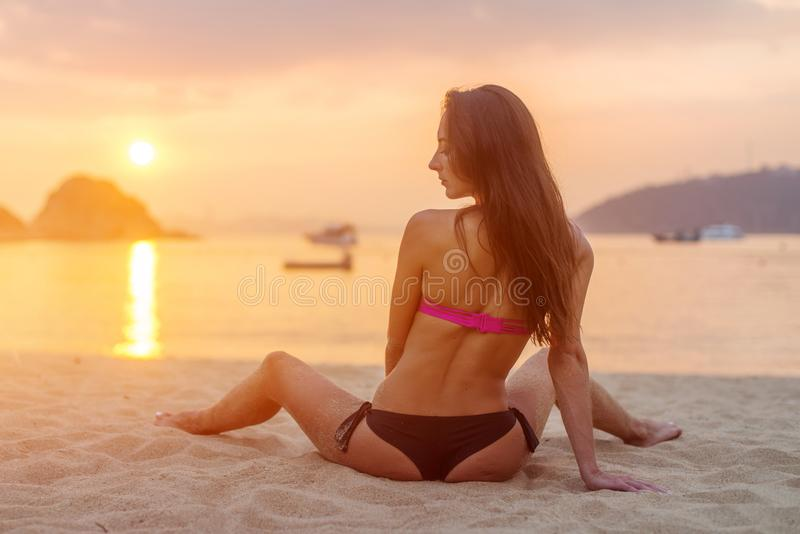 Vista posterior del modelo femenino delgado que se sienta en el bikini que lleva de la costa que mira lejos durante salida del so foto de archivo