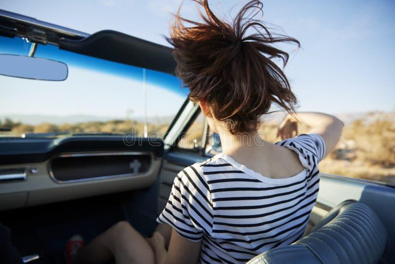 Vista posterior del pasajero femenino en viaje por carretera en coche convertible clásico foto de archivo
