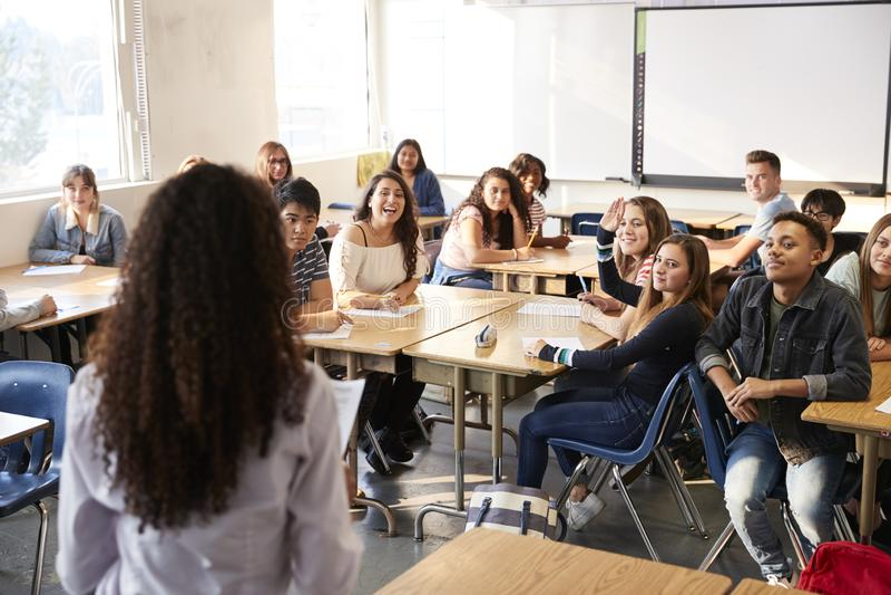 Vista posterior del profesor de secundaria de sexo femenino Standing At Front Of Class Teaching Lesson fotos de archivo libres de regalías