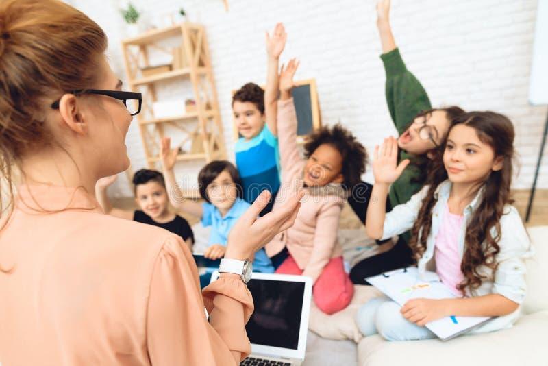 Vista posterior del profesor que enseña a la lección en escuela primaria Concepto de la educación primaria del ` s de los niños imagen de archivo