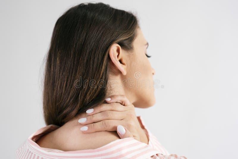 Vista posterior del sufrimiento de la mujer joven del dolor de cuello fotografía de archivo libre de regalías