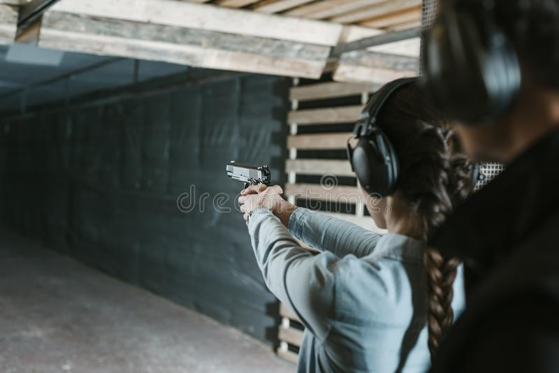 vista posterior del tiroteo de la muchacha con el arma foto de archivo
