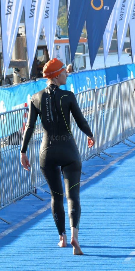 Vista posterior del triathlete femenino que lleva caminar negro del traje de baño imagenes de archivo