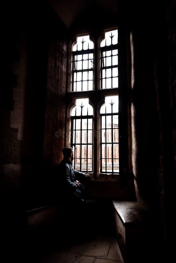 Vista posterior en la silueta del hombre que se sienta en la oscuridad que mira a través de ventana brillante vieja con los rayos fotografía de archivo libre de regalías