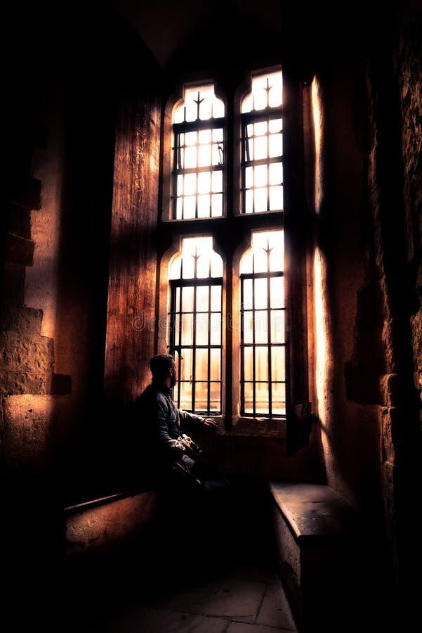 Vista posterior en la silueta del hombre que se sienta en la oscuridad que mira a través de ventana brillante vieja con los rayos foto de archivo libre de regalías