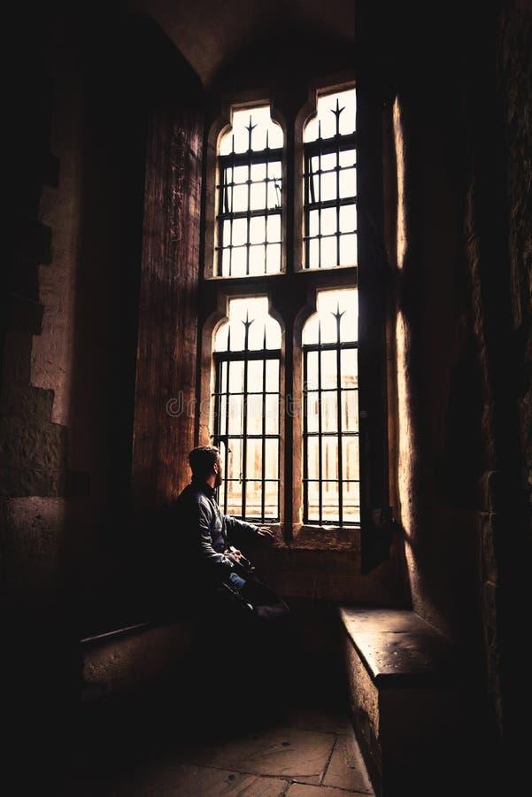 Vista posterior en la silueta del hombre que se sienta en la oscuridad que mira a través de ventana brillante vieja con los rayos imagenes de archivo