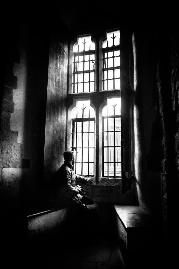 Vista posterior en la silueta del hombre que se sienta en la oscuridad que mira a través de ventana brillante vieja con los rayos imágenes de archivo libres de regalías
