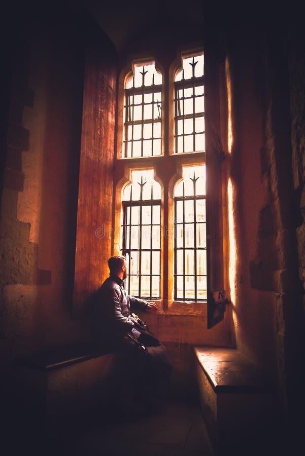 Vista posterior en la silueta del hombre que se sienta en la oscuridad que mira a través de ventana brillante vieja con los rayos fotografía de archivo